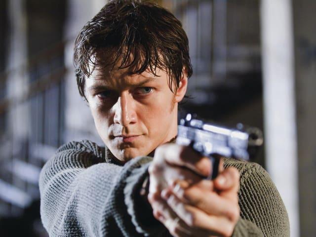 James McAvoy zielt mit einer Pistole.