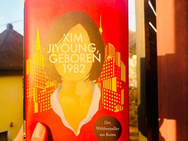 Annette König hält das Buch «Kim Jiyoung geboren 1982» von Cho Nam-Joo an die Sonne