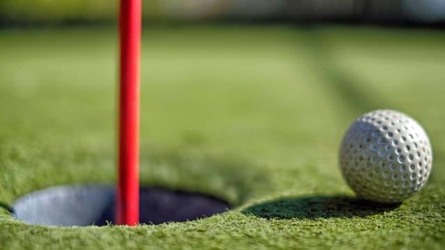 Golfball liegt vor Loch