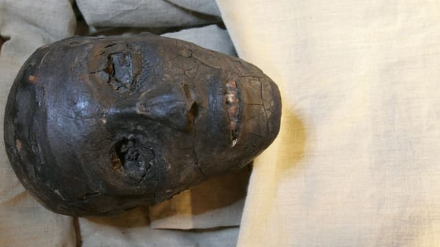 Die Mumie von Tunanchum unter einem weissen Tuch.