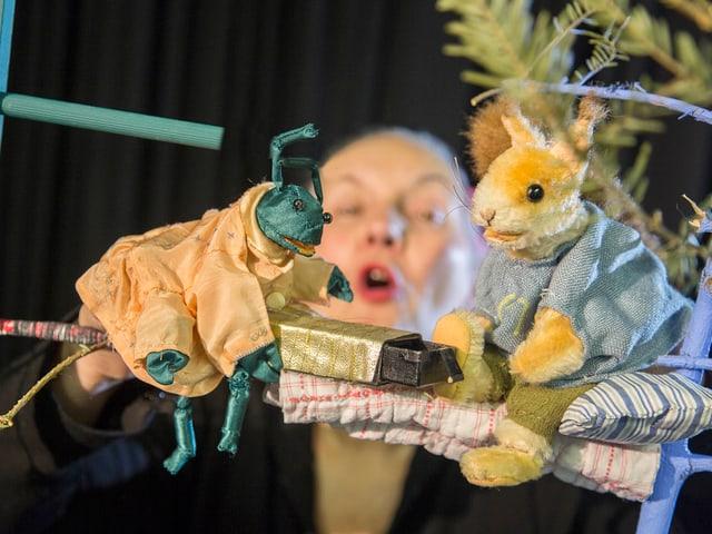 Ein Eichhörnchen wird von einem anderen Tier beschenkt, im Hintergrund verschwommen Puppenspielerin Gysin.