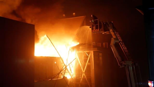 Feuwehrleute im Dunkeln bekämpfen vom Dach des Nachbarhauses aus das lichterloh brennende, zum Teil schon eingstürzte Gebäude.