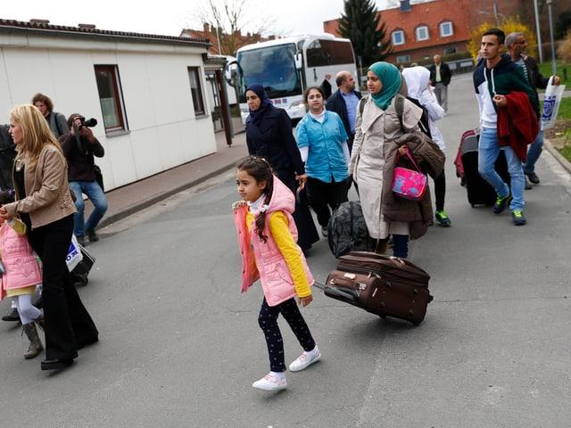 Flüchtlinge die aus einem Bus steigen und in ein Flüchtlingslager laufen.
