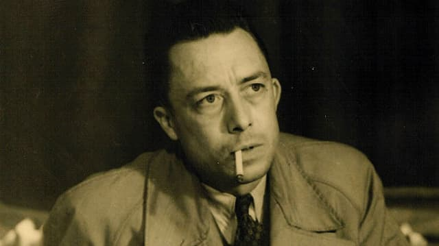 Albert Camus in einer Porträtaufnahme. Im Mantel an einem Tisch sitzend, mit Zigarette im Mund.