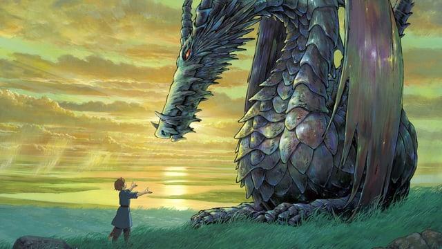 Ein kleiner Junge neben einem grossen Drachen.