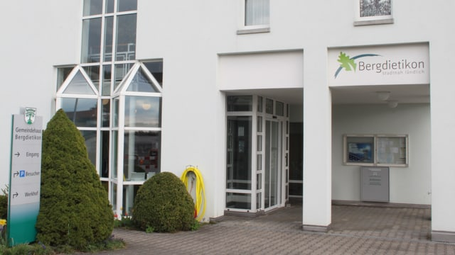 """Weisses Gebäude mit Eingangschild """"Bergdietikon""""."""
