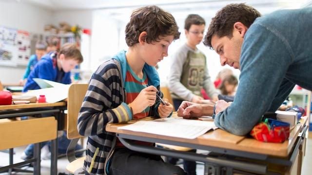 Ein Lehrer beut sich über einen Tisch, daran sitzt ein Junge, der Aufgaben löst.