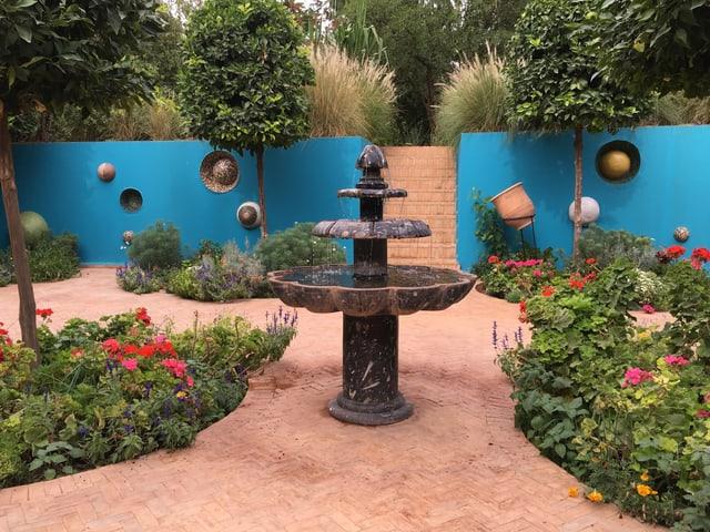 Ein Brunnen vor einer türkisen Wand, der umhüllt ist von Planzen und Blumen.