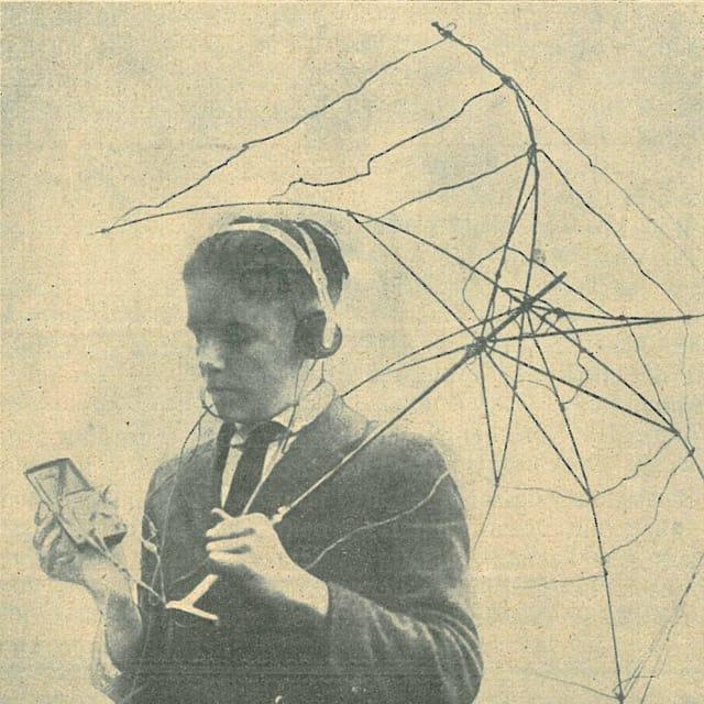 Junge mit ausrangiertem Gerüst eines Regenschirmes, Empfänger in der Hand und Kopfhörer.