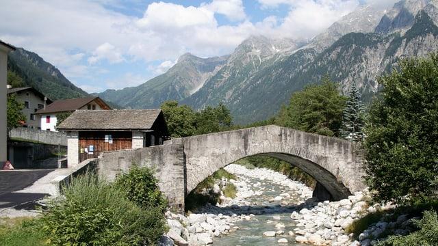 Eine Steinbrücke überquert ein steiniges Bachbett.