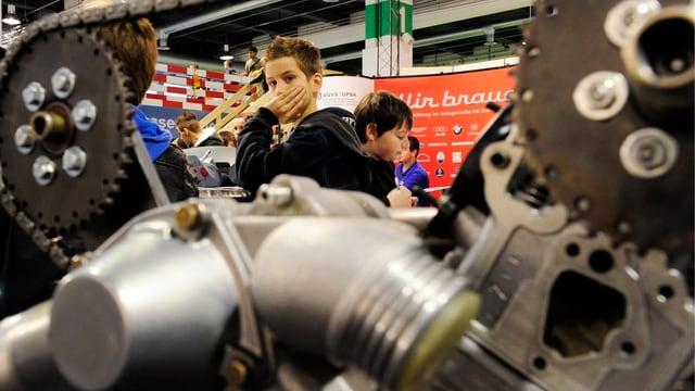 Ein Junge stützt den Kopf auf die Hand, im Vordergrund eine Maschine mit Zahnrädern.