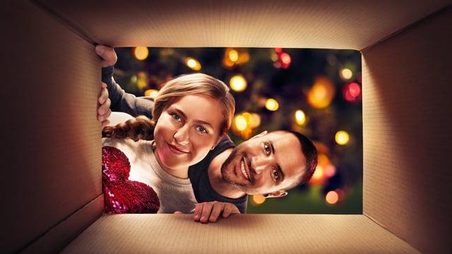 Duas persunas miran en ina scatla per il pachet da Nadal.