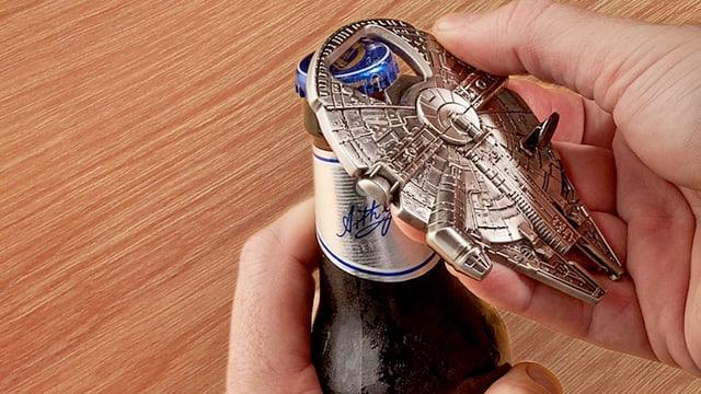 Zwei Hände die eine Glasflasche mit einem Flaschenöffner öffnen