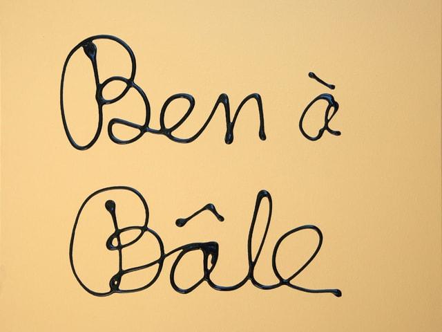 Auf gelblichem Hintergrund steht in schwarzer Schrift «Ben à Bâle».