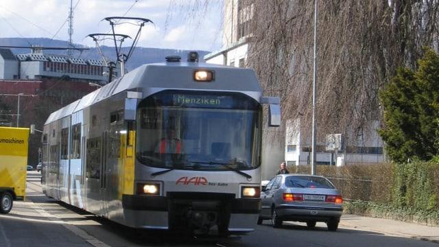 Tram fährt neben Auto.