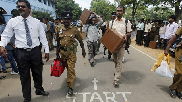 Polizisten eskortieren Helfer, die die Urnen zur Wahlbehörde bringen. (reuters)