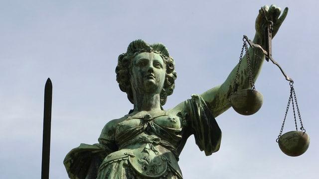 Statue der Justitia von unten fotografiert, im Hintergrund Himmel. Justita mit der Waage in der einen und einem Schwert in der anderen Hand.