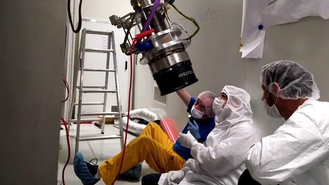 Drei Forscher in Schutzanzügen schauen auf ein grosses objektiv-ähnliches Objekt.