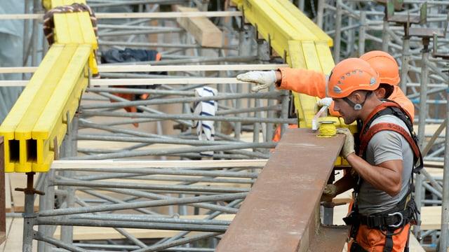 Zwei bauarbeiter mit Helm sind mit einem Stahlträger beschäftugt.