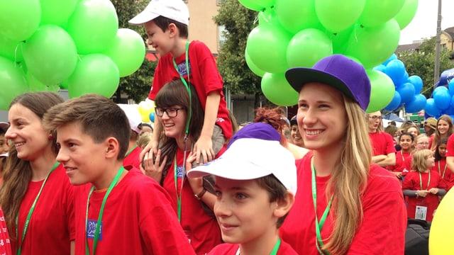 Im Vordergrund sieht man 6 Kinder, die alle rote T-Shirts tragen und lachen. Im Hintergrund sieht man noch viele weitere Kinder und Luftballone.