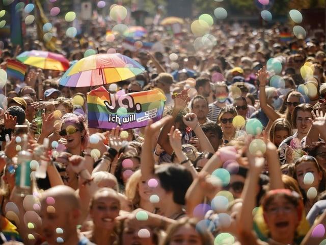 Menschen in einem Demonstrationszug. Man sieht Regenbogenfahnen.