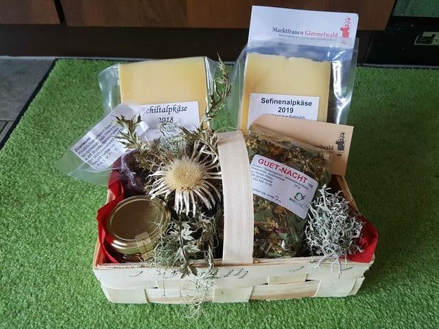 Käse, Wurst, Honig und Tee in einem Geschenkkorb.