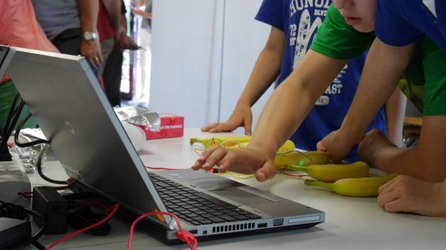 Mehrere Kinder beugen sich über einen Computer, Bananen liegen davor auf dem Tisch.