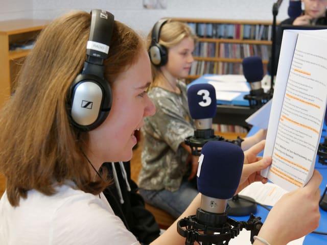 Ein Mädchen liest vor dem Mikrofon das Skript