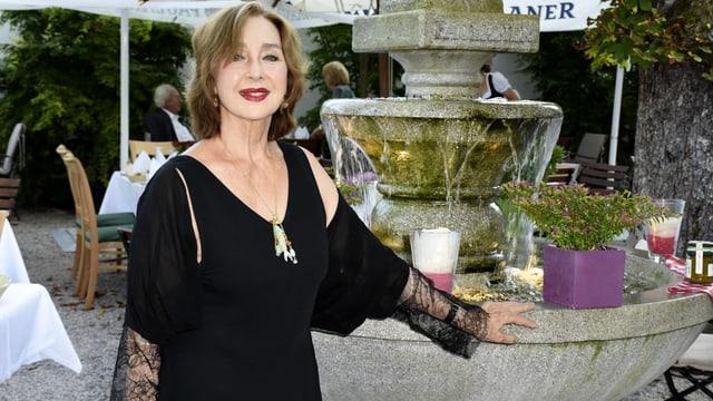 Christine Kaufmann posiert vor einem Brunnen.