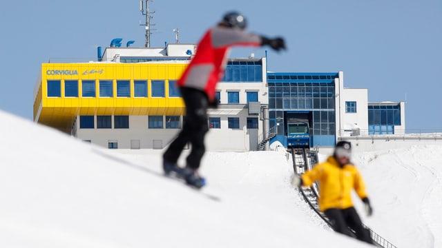 staziun da la pendiculara Corviglia cun skiunz e snowboardist davatvart