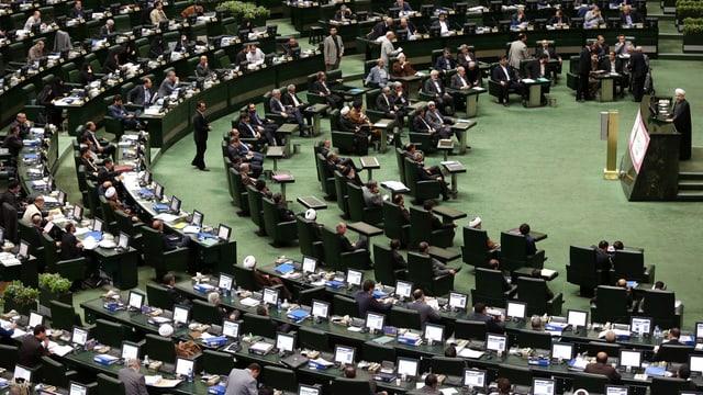 Parlamentaris sesan avant ils laptops e taidlan in che discurra.