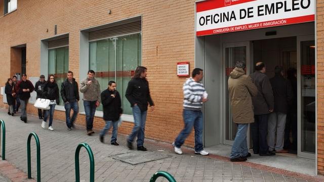 Zu sehen sind Menschen vor einem Arbeitsamt in Spanien.