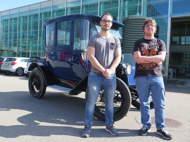Zwei Männer vor altem Elektromobil