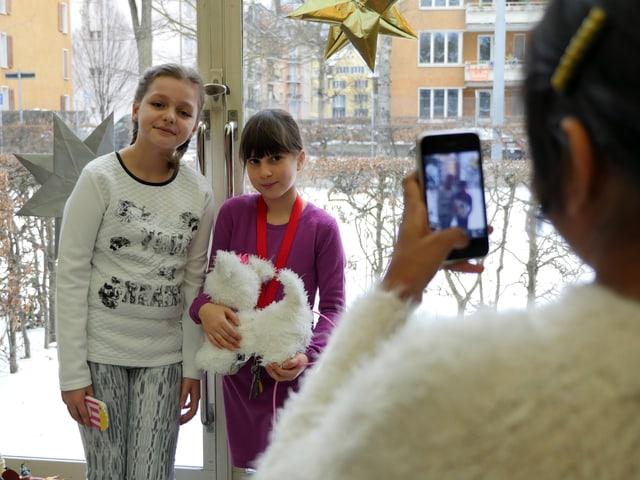 Ein Mädchen macht ein mit dem Smartphone ein Bild von zwei Freundinnen.