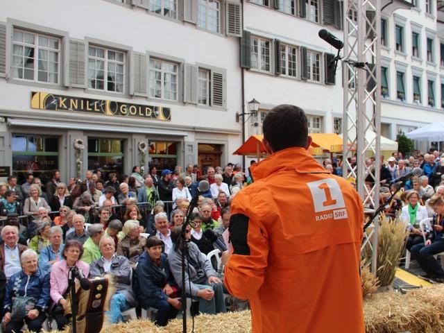 Adrian Küpfer von hinten mit Blick auf Publikum vor der Bühne.