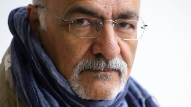 Porträtfoto von Mahmoud Hosseini Zad mit Schal und Brille.
