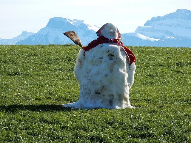 Leicht angeschmolzener Schneemann auf grüner Wiesi, im HIntergrund verschneite Berge.