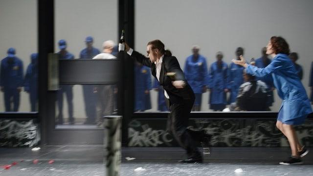Mann in Smoking rennt mit Sektflasche, hinter ihm her eine Frau, im Hintergrund Menschen in blauen Kitteln.