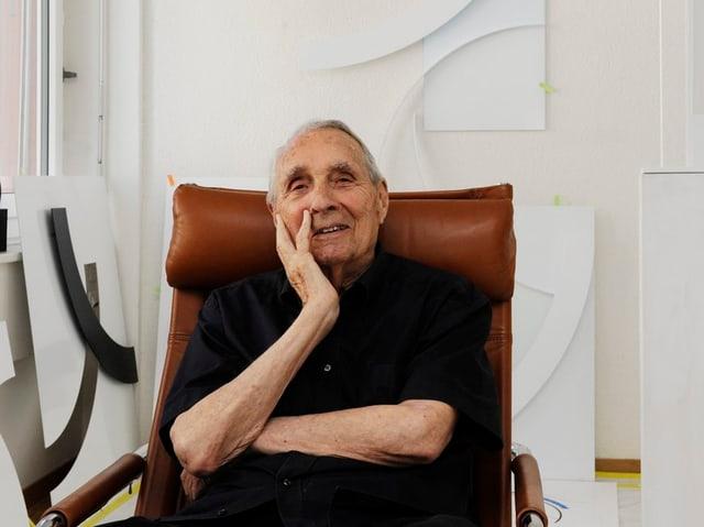 Gottfried Honegger, aufgenommen an seinem 95. Geburtstag, sitzt in einem Sessel in seinem Atelier, Werke von ihm im Hintergrund an der Wand.