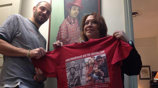 Oliver Streuli und Sozialarbeitern Marianne Diaz vor einem Porträt Bloodhounds in Öl.