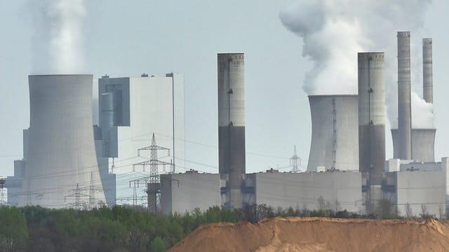 Fünf rauchende Atomkraftwerke in einer düsteren Landschaft.