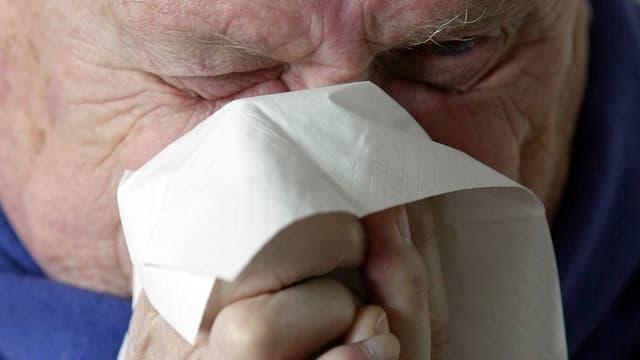 Mann in Grossaufnahme mit blauem Schal schneuzt sich in ein Papiertaschentuch