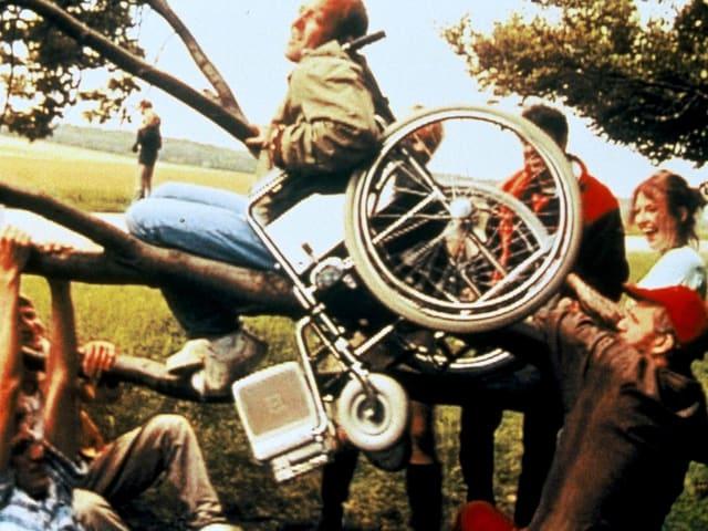 Eine Gruppe junger Leute heben einen jungen Mann, der in einem Rollstuhl sitzt, mitsamt Rollstuhl in die Luft.
