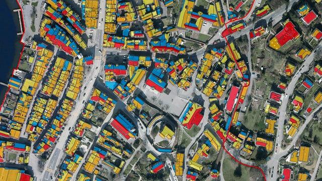 Flugaufnahme mit rot, orange, gelb oder blau gefärbten Dächern.