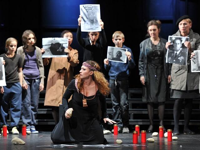 Mezzosopranistin Sanja Anastasia als Wahrsagerin Ulrica kauert vor dem Chor im Theater Basel.