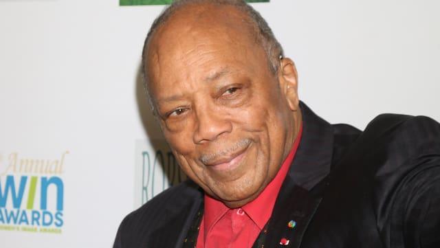 Quincy Jones in einem schwarzen Anzug mit rotem Hemd vor einer weissen Fotowand.