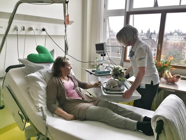 Spital-Mitarbeiterin serviert einer Patientin das Essen.