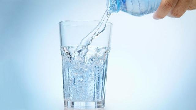 Sprudelwasser wird in ein Glas geleert.