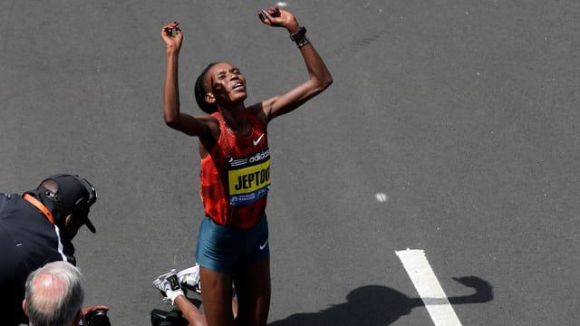 Die Kenianerin Rito Jeptoo auf den Knien mit erhobenen Händen nach dem Sieg beim Boston-Marathon 2014