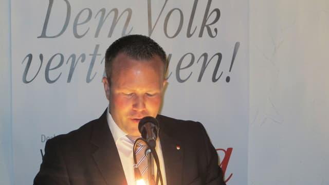 """Silvio Jeker am Rednerpult, im Hintergrund der SVP-Slogan """"Dem Volk vertrauen""""."""
